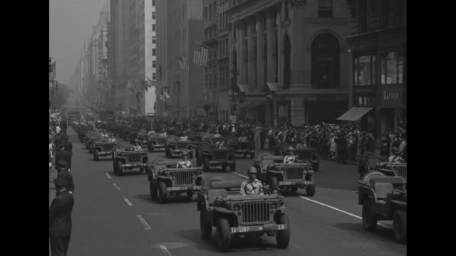 vs troops march on fifth avenue in manhattan during rally to kick off third war loan drive for world war ii war bonds / women watch from upper story... - ジープ点の映像素材/bロール