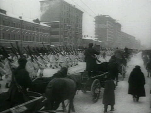 troops marching in city snow with tramway moving audio/ russia - 路面軌道点の映像素材/bロール