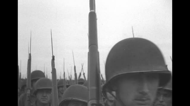 VS US troops of the 2nd Armored Division march in review as they approach pass bearing bayoneted rifles / VS color guard with fluttering US flag / CU...