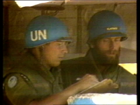 UN troops on border patrol 1982 Israeli tanks along past UN checkpoint Interview Parsons LIBRARY People along in street women in car truck along gun...