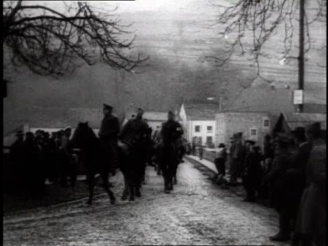 vidéos et rushes de troops on horseback crossing stone bridge toward small gathering of people / germany - 1918