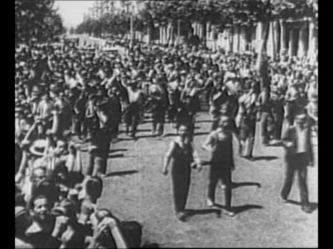 troops on ship wave as they sail past camera / people march in street as spectators cheer wave / military planes in sky during spanish civil war /... - 1937 stock-videos und b-roll-filmmaterial