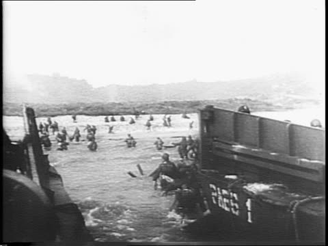 troops parading ashore on dday / troops and equipment on shore / man gets up and walks to control board / man moves marker on control board / gas... - map marker stock videos and b-roll footage