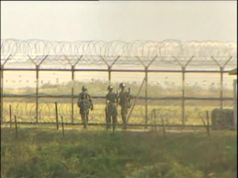 Troops patrol border between North and South Korea as civilians look across through binoculars and peer through fence South Korea 10 Oct 06