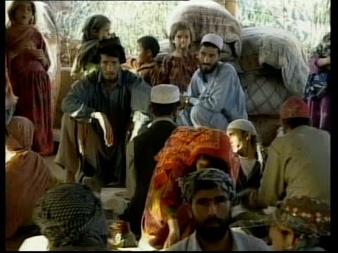Peshawar GVs Afghan refugees in camp BV Man cooking bread in oven MSs Children in refugee camp