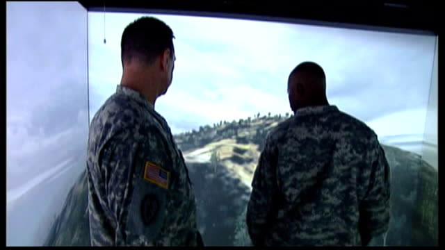 US troops train for Afghanistan IED threat Reporter standing with computer designers in front of large screens showing virtual reality version of IED...