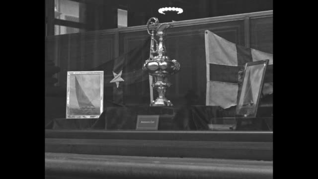 trophy labeled america's cup on display with two photos of yachts and two flags / cu america's cup trophy - skåp med glasdörrar bildbanksvideor och videomaterial från bakom kulisserna