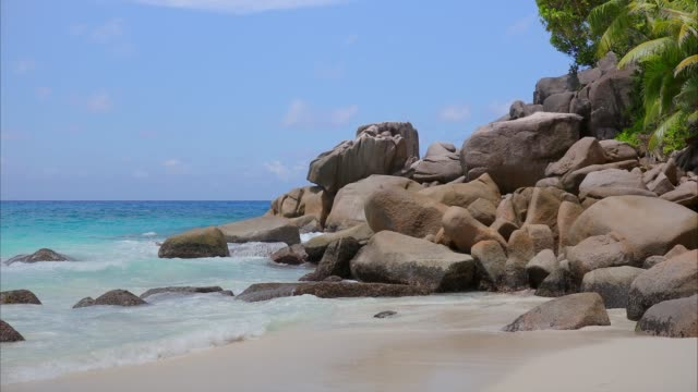 tropical beach anse georgette with typical granite rock formations on praslin island , granitic seychelles , archipelago country in the indian ocean - granite rock stock videos & royalty-free footage