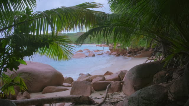 tropical beach anse lazio with typical granite rock formations and palm trees on praslin island , granitic seychelles , archipelago country in the indian ocean - granite rock stock videos & royalty-free footage