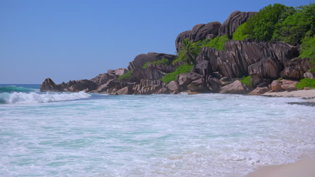 tropical beach grand anse with typical granite rock formations on la digue island , granitic seychelles , archipelago country in the indian ocean - granite rock stock videos & royalty-free footage