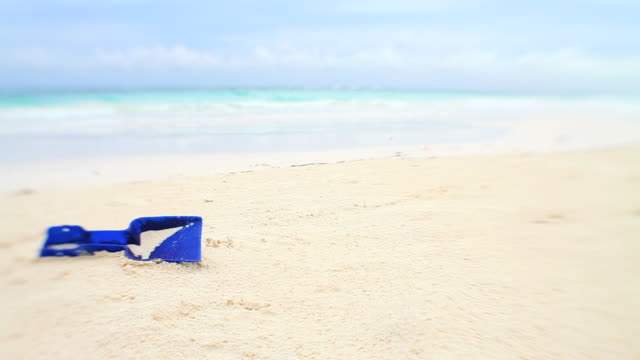 Tropical beach holiday blue spade forgotten in sand