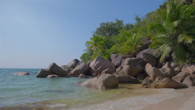 tropical beach petite anse kerlan with typical granite rock formations and palm trees on praslin island , granitic seychelles , archipelago country in the indian ocean - granite rock stock videos & royalty-free footage