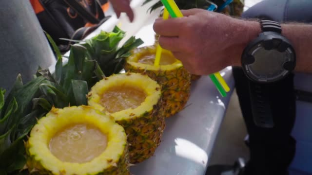 tropical drinks inside whole pineapples are stirred and finished - pineapple stock videos & royalty-free footage