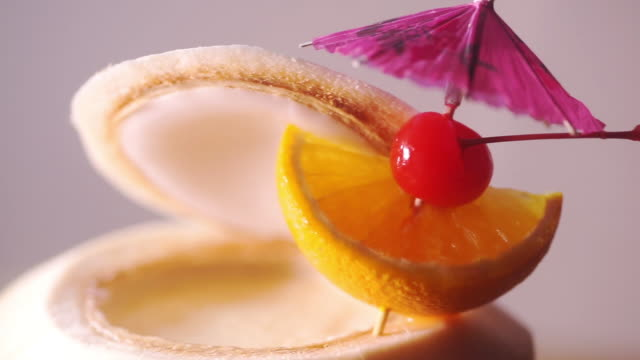 tropical fresh coconut cocktail decorated with umbrella, slices of orange and maraschino cherry. - tropical cocktail stock videos & royalty-free footage