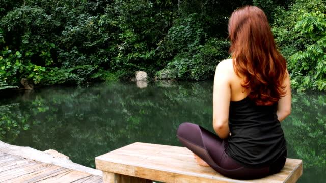 vídeos de stock, filmes e b-roll de meditação de jardim tropical - cabelo ruivo