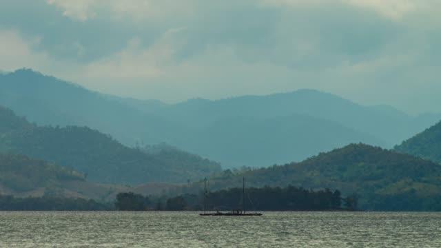 tropische see mit silhouette gebirgshintergrund, zeitraffer-video - tropischer baum stock-videos und b-roll-filmmaterial