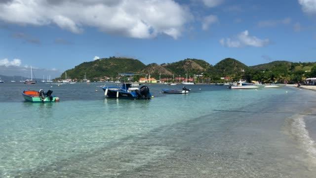 vidéos et rushes de tropical les saintes bay, beach, calm water, small boats, terre de haut island, iles des saintes, guadeloupe, west indies, caribbean, central america - guadeloupe