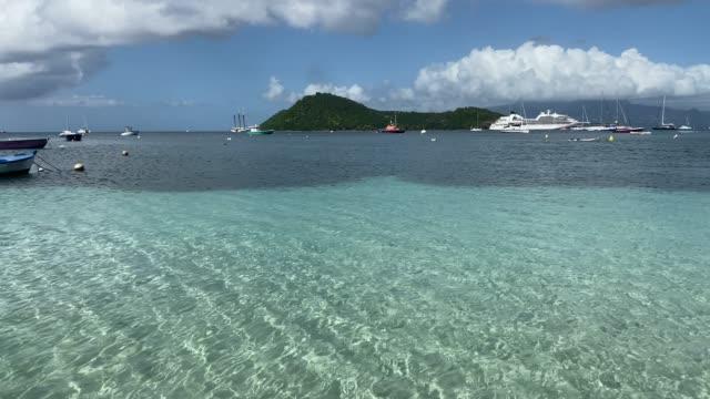 vídeos de stock e filmes b-roll de tropical les saintes bay, ripples on calm turquoise water, small boats, cruise ship, terre de haut island, guadeloupe, west indies, caribbean, central america - territórios ultramarinos franceses