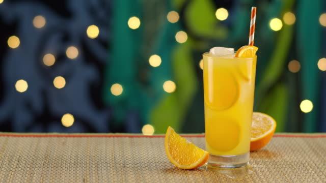 tropical orange drink splashing in ice - tropical drink stock videos & royalty-free footage