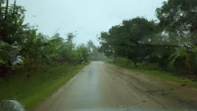 Tropical rain seen through car window while driving in rural area