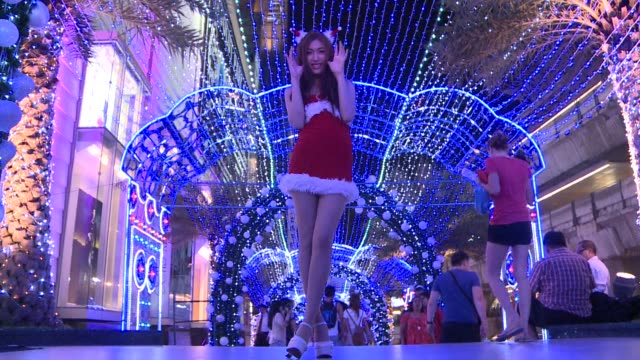 tropical thailand might be buddhist but people are embracing the festive spirit wearing santa claus hats and queueing to have their photo taken in... - soundtrack stock videos & royalty-free footage
