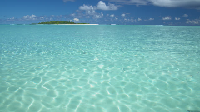 ws, tropical water with island in distance, aitutaki lagoon, aitutaki, cook islands - aitutaki lagoon stock videos & royalty-free footage