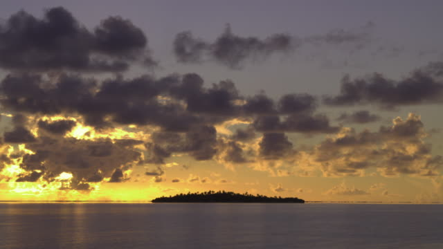 t/l, ws, tropical water with island in distance at sunrise, aitutaki lagoon, aitutaki, cook islands - aitutaki lagoon stock videos & royalty-free footage
