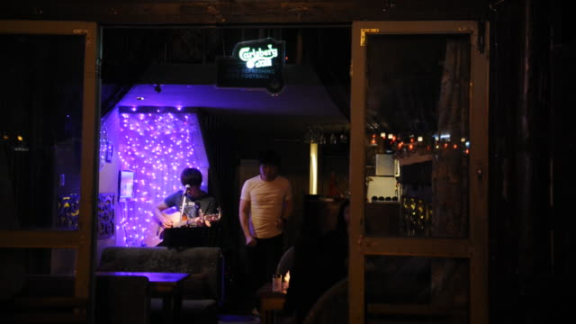 A troubadour performs at a Lake Houhai bar.