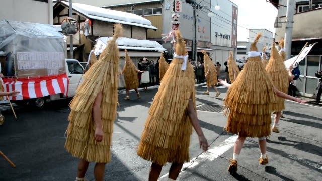 a troupe of dancers in pointy straw capes gathered to skip on street corner as residents doused them with freezing water shot on february 112016 in... - yamagata prefecture stock videos & royalty-free footage