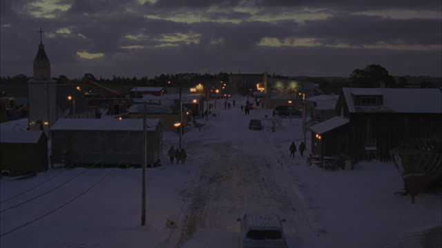 A truck and several pedestrians travel over snow covered streets in a small village.