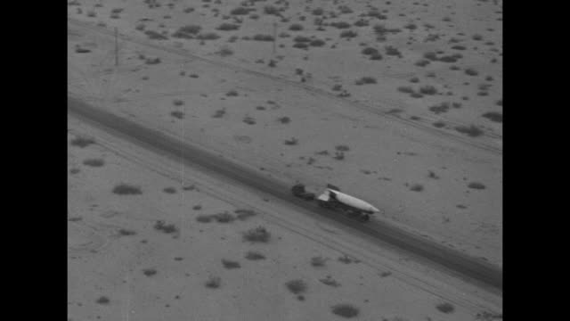 truck and trailer transport a v-2 rocket across sandy terrain / pan across launch pad and buildings nearby / note: exact day not known - note pad点の映像素材/bロール