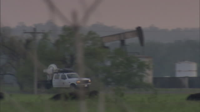 a truck carrying radar equipment drives across a farmland road to collect data on tornadoes. - meteorology stock videos & royalty-free footage