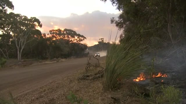 truck coming down a road on kangaroo island, smoke and fire in the foreground. - environment or natural disaster or climate change or earthquake or hurricane or extreme weather or oil spill or volcano or tornado or flooding stock videos & royalty-free footage