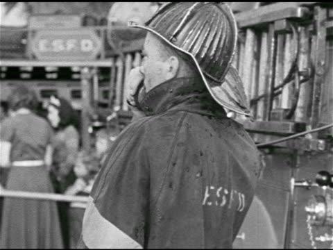 truck & crew, driver using two-way radio. fireman talking on radio w/ woman & few children standing bg. ops center: fire chief announcing 'kids... - whatif点の映像素材/bロール