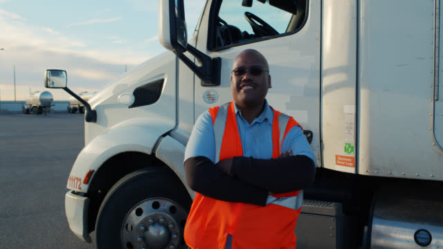 vídeos y material grabado en eventos de stock de truck driver in high vis getting out of cab and posing - camionero