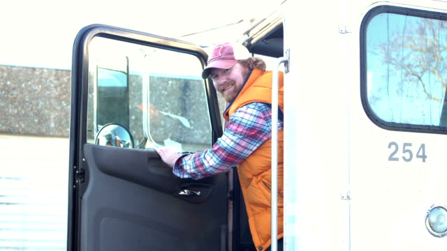 truck driver leans out door to smile at the viewer - trucker cap stock videos & royalty-free footage