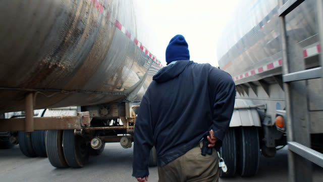 truck driver looking under tanker - only mid adult men stock videos & royalty-free footage