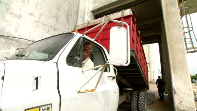 vidéos et rushes de a truck driver lowers the bed of his dump truck. - silo