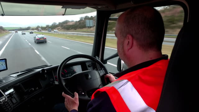 truck driver sat behind the steering wheel driving - articulated lorry stock videos and b-roll footage