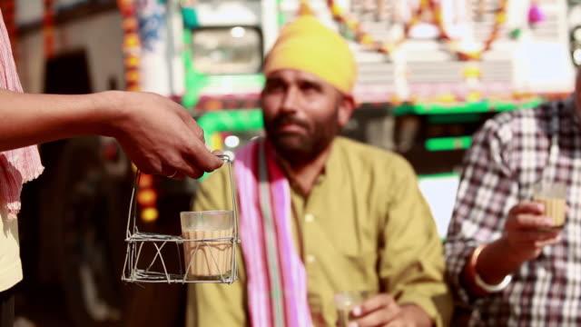 Truck drivers drinking tea at a tea stall, Ballabgarh, Haryana, India