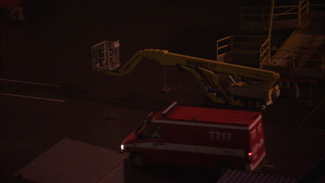 a truck drives across a loading dock and past a cherry picker. - cherry picker stock videos & royalty-free footage