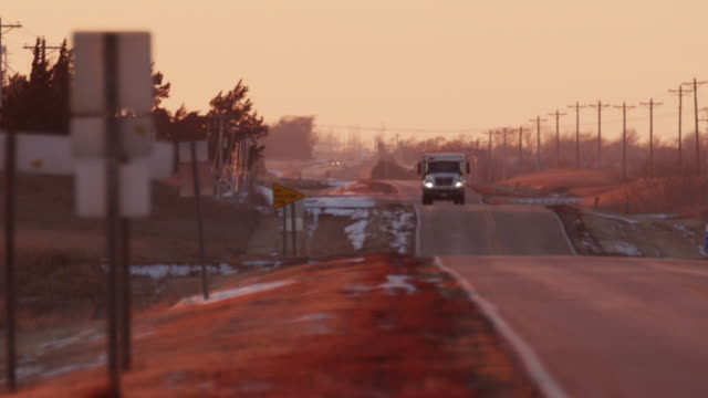 vidéos et rushes de a truck drives down a rolling highway toward camera with telephone poles in the distance at sunset. - véhicule utilitaire léger