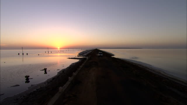 a truck drives on a causeway during a sunset. - causeway stock videos & royalty-free footage