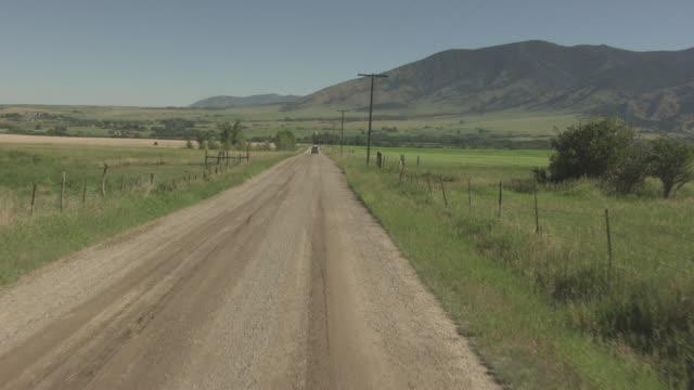 vídeos y material grabado en eventos de stock de truck drives on a dirt road - helio