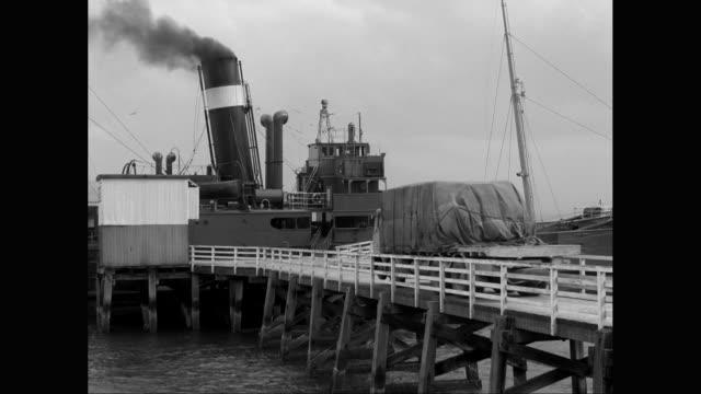 vídeos de stock e filmes b-roll de ms truck drives on dock to waiting cargo ship / united states - vedação