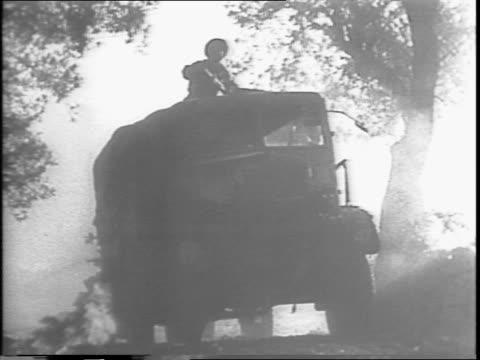 a truck drives through trees / a soldier raises his rifle while riding on top of the truck / an armored vehicle drives through the forest / smoke... - anno 1943 video stock e b–roll
