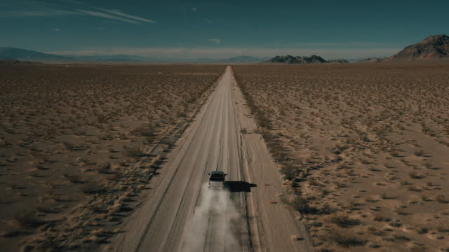 stockvideo's en b-roll-footage met truck driving across a remote landscape on a dry dirt road filmed by a drone following behind, nevada, united states of america - onverharde weg