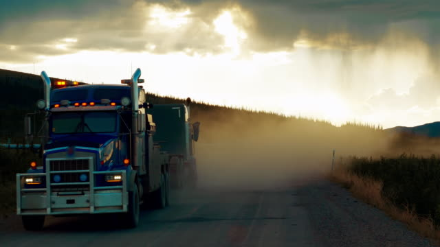 truck driving dalton highway at sunset in a stormy day and passing oil pipelines in alaska - schotterstrecke stock-videos und b-roll-filmmaterial