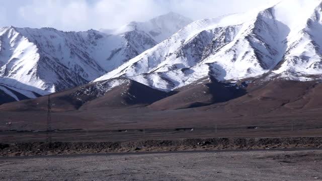 truck driving on highway through tibetan plateau - tibetan plateau stock videos & royalty-free footage