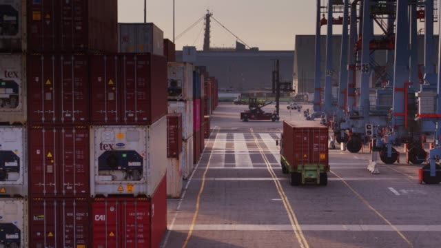 truck driving past container crane in port terminal - aerial - cargo container stock videos & royalty-free footage
